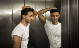Handsome young man leaning against mirror inside an elevator (lift) Royalty Free Stock Photos
