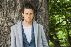 Handsome Young Man Leaning Against Tree Royalty Free Stock Image