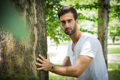 Handsome young man leaning against tree Stock Image