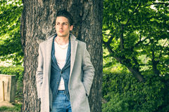 Handsome young man leaning against tree Royalty Free Stock Photos