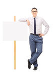 Handsome young man leaning on a blank poster Royalty Free Stock Image