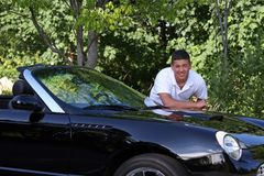 Handsome Young man leaning on Car. A handsome young man leaning on a luxury black convertible royalty free stock image