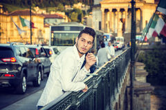Handsome Young Man Leaning on City Bridge Handrail. Handsome Young Man Leaning Against Metal Handrail at the River in European City, with Cars Behind Him. Turin Royalty Free Stock Photo
