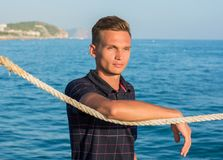 Handsome young man leans on a rope on a sea background Royalty Free Stock Photos