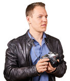 Handsome young man with a leather jacket holding a vintage camera. Isolated Royalty Free Stock Images