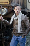 Handsome young man in leather jacket and jeans next to old train. Attractive young man in leather jacket and jeans next to old train looking at camera Stock Image