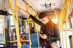 Handsome young man in leather jacket using smartphone. In bus Stock Photos