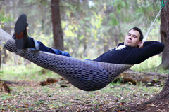 Handsome young man lies in hammock in woods Royalty Free Stock Image