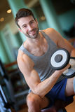Handsome young man lifting weights in a fitness club Royalty Free Stock Image
