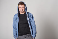 Handsome young man with light beard in blue hoodie,  on gray bac Royalty Free Stock Image