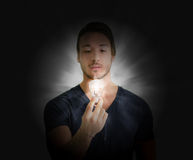 Handsome young man with lightbulb Stock Images