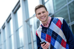 Handsome young man listening to music. Happy young man listening to music on his mobile phone Stock Images