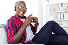 Handsome young man listening to music with headphones at home. Portrait of handsome young man listening to music with headphones at home Stock Photos