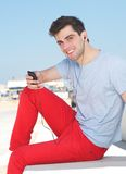 Handsome young man listening to music on mp3 player Stock Photo