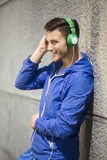 Handsome young man listening to music outdoors Royalty Free Stock Images