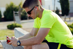 Handsome young man listening to music after running. Royalty Free Stock Photography