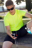 Handsome young man listening to music after running. Stock Photos