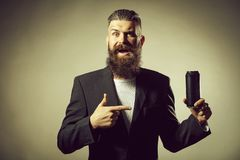 Bearded man with beer tin can. Handsome young man with long beard and moustache in black jacket holding tin beer can bottle in studio on grey background stock photography