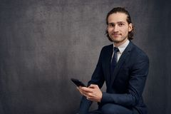 Handsome young man with long hair holding a smartphone royalty free stock image