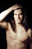 Handsome young man with long hair naked torso on black background Stock Photo