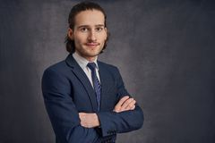 Handsome young man with long haircut in business suit stock photography