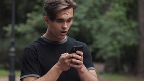 Handsome Young Man Looking Amazed Scrolling the Phone and Saying Wow Standing in Park. stock footage