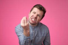 Handsome young man looking angry showing italian gesture over pink background. royalty free stock photos