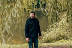 Handsome young man looking away while walking. In autumn park stock photo