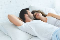 Handsome young man looking at beautiful smiling girlfriend. While lying together in bed royalty free stock image