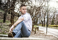 Handsome young man looking at camera in park Stock Photos