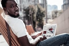 Handsome young man looking into camera while using laptop. Busy working. Selective focus on a millennial guy wearing casual attire sitting outdoors and turning Royalty Free Stock Photos