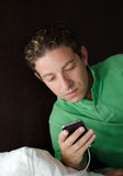 Handsome young man looking at cell phone at night in bed Stock Photo