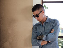 Handsome young man looking down. Good looking male model with sunglasses looking down, with large copy-space Stock Image