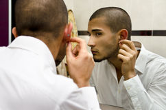 Handsome young man looking at ear piercing Stock Images