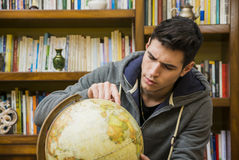 Handsome young man looking at a globe indoors at home Stock Photo