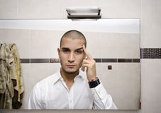 Handsome young man looking at himself in bathroom mirror Royalty Free Stock Images