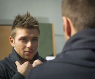 Handsome young man looking at himself in mirror. With a grin stock photos