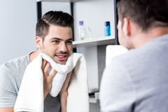 Wiping face. Handsome young man looking at mirror and wiping face with towel Stock Images
