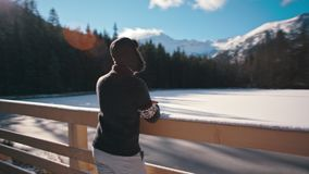 Handsome Young Man is Looking at Mountain Lake in Winter with Sun Lense Flare. Handsome Young Man is Admiring the Mountain Lake under snow in Winter with Amazing stock footage