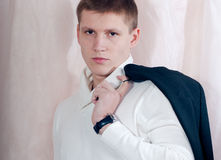 Handsome young man looking serious, holding jacket Stock Image
