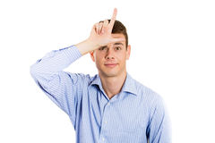 Handsome young man with loser sign on forehead Royalty Free Stock Photo