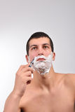 Handsome young man with lots of shaving cream on his face prepar Stock Photography