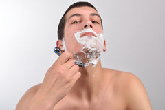 Handsome young man with lots of shaving cream on his face prepar Stock Photos