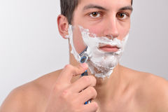 Handsome young man with lots of shaving cream on his face is sha Royalty Free Stock Photo