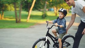 Handsome young man loving father is teaching his small son to ride bicycle in park on summer day, boy is riding bike. Handsome young man loving father is stock video footage
