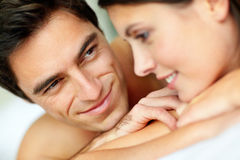 Handsome young man lying on bed with his wife Royalty Free Stock Photography