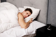 Handsome young man lying in bed. Royalty Free Stock Images