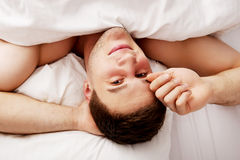 Handsome young man lying in bed. Royalty Free Stock Photography
