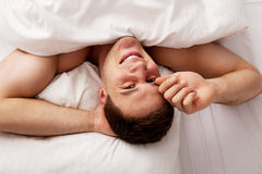 Handsome young man lying in bed. Stock Photo