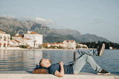 Handsome young man Lying and dreaming with laptop computer near. The sea Stock Photo